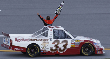 Mike Wallace takes the checkered flag at Talladega in 2011 in the Anderson's Maple Syrup / KHI Chevy Silverado.